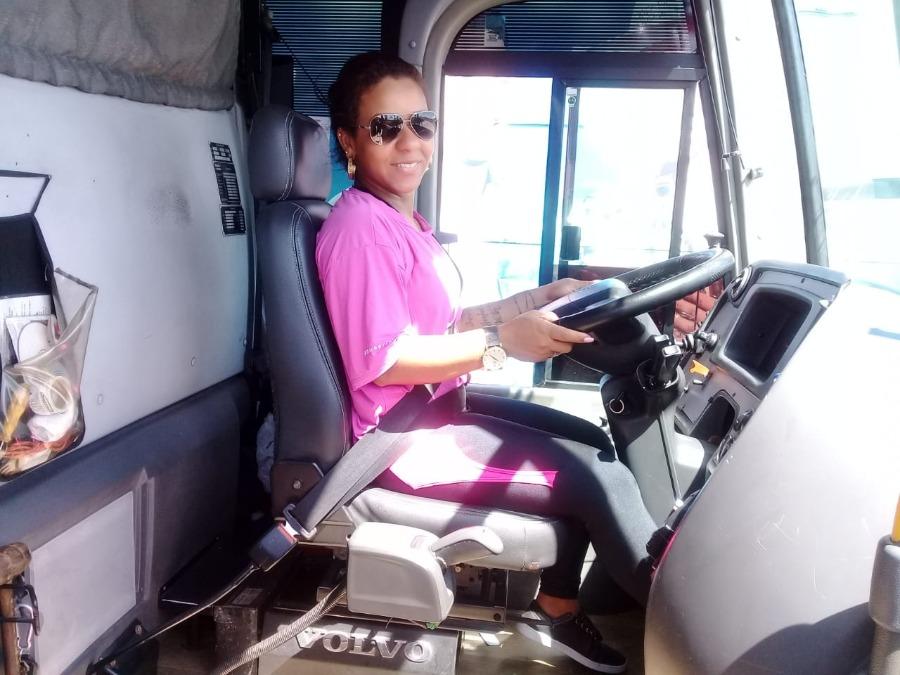 Júnia, mulher motorista de ônibus, dentro de um ônibus, posicionada atrás do volante