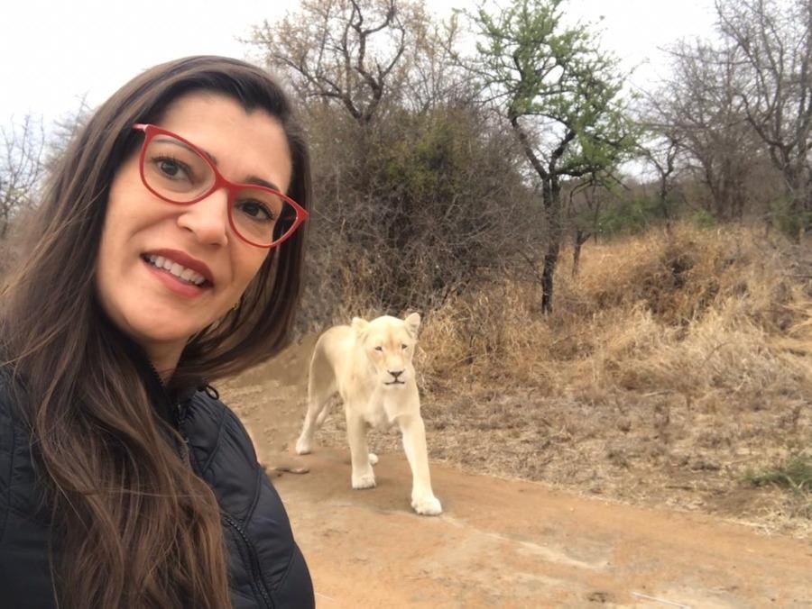 Melani Guedes em sua viagem para a África com um felino de grande porte branco