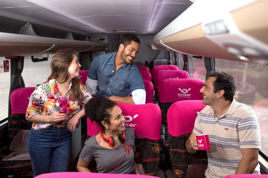 quatro pessoas alegres conversando dentro de um ônibus Buser após ter planejado a viagem com dicas