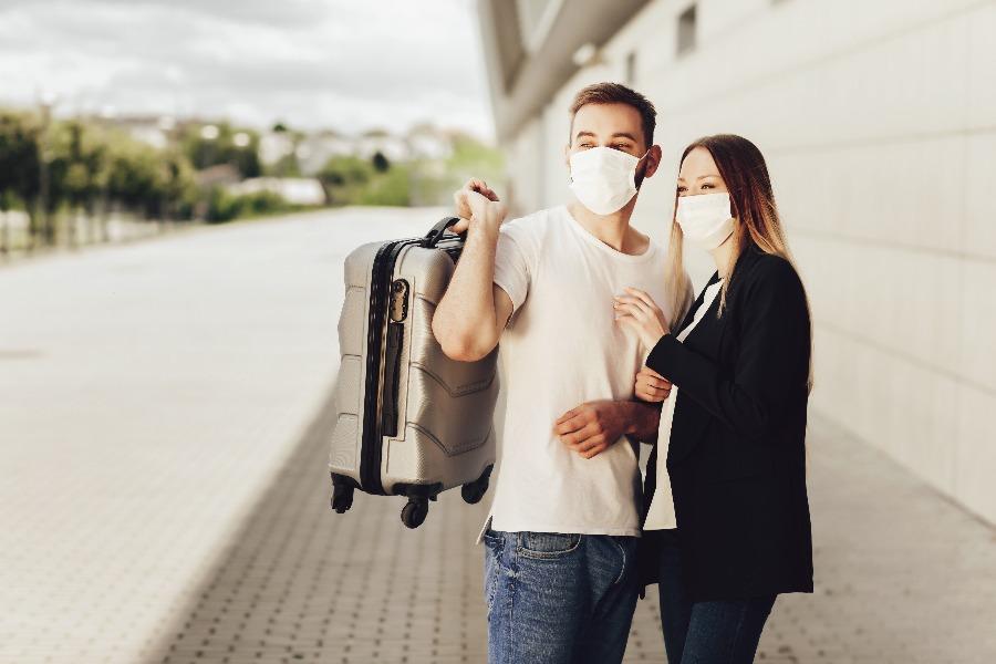casal com malas e máscaras se preparando para viajar de ônibus durante a pandemia de coronavírus