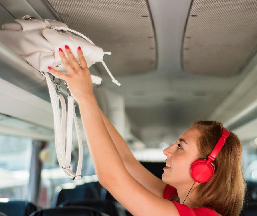 foto de mulher colocando a mala de mão no bagageiro do ônibus