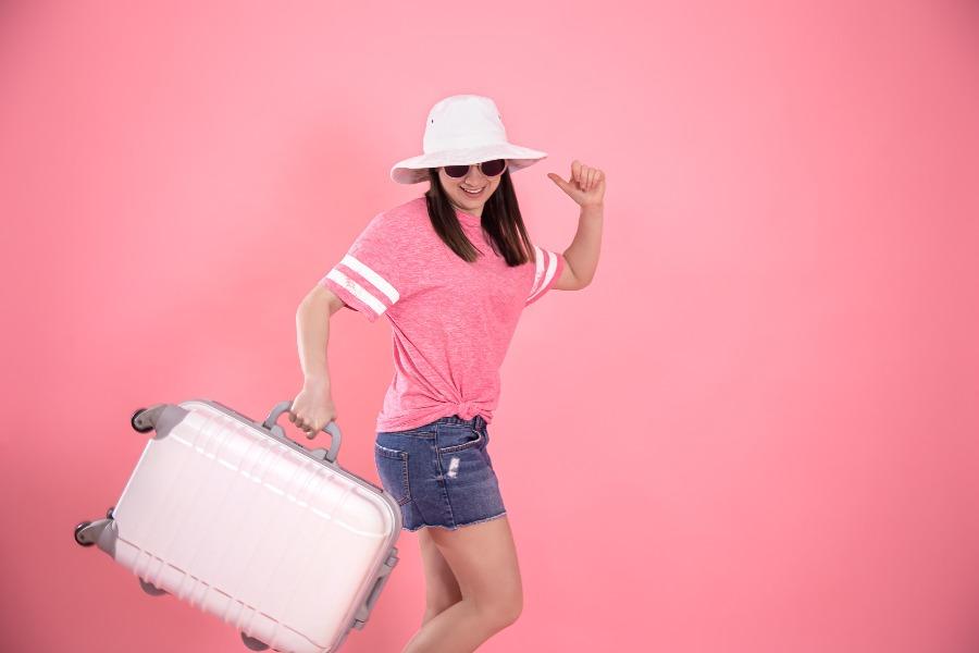 Mulher em fundo rosa carregando uma mala com as mãos e que poderia ser uma mala de mão. Demonstrando o que levar na mala de mão