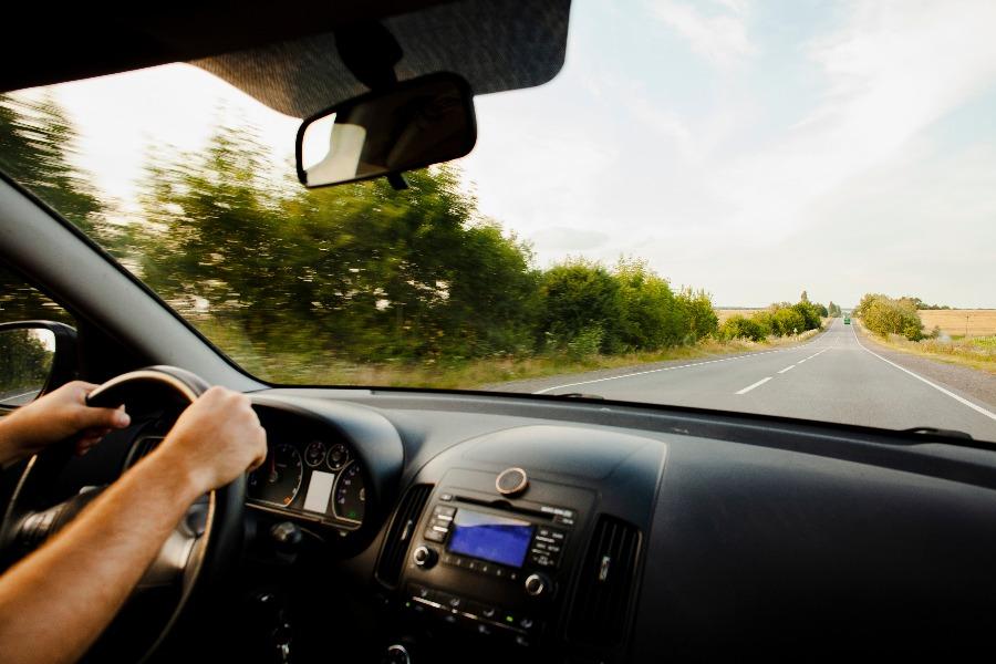 homem com as mãos no volante viajando de carrro