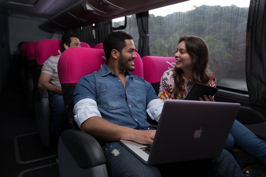 poltrona de ônibus leito-cama. Na foto, home negro com um notebook viajando ao lado de uma mulher morena de cabelos lisos.