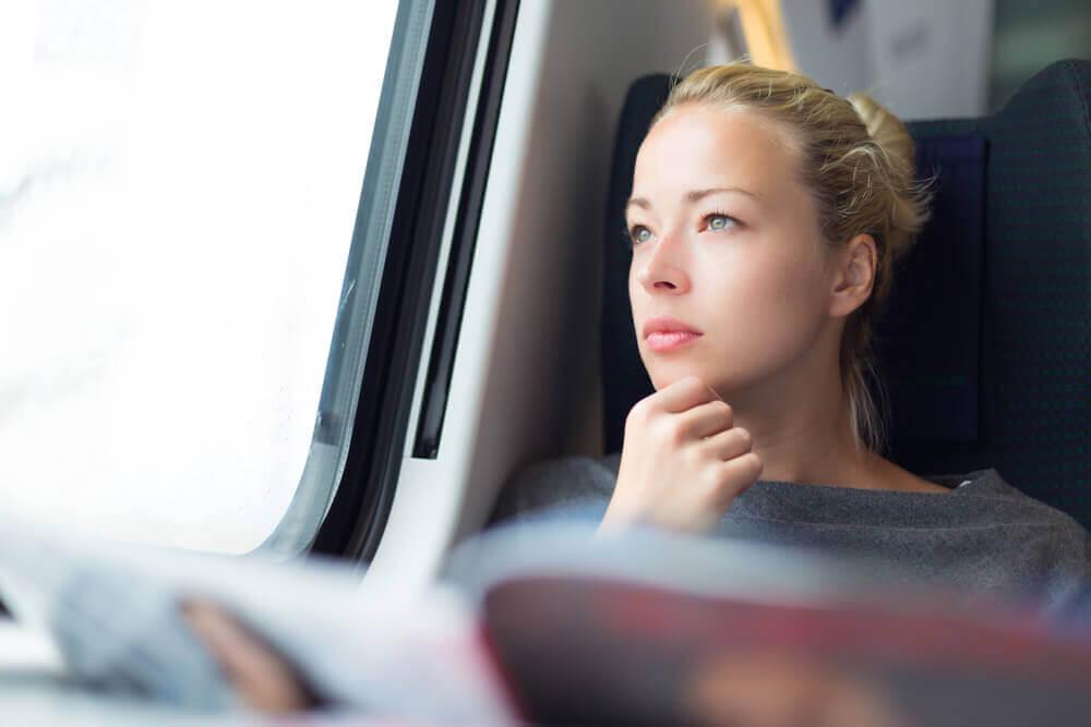 mulher branca olha para o horizonte a fim de evitar o enjoo na viagem