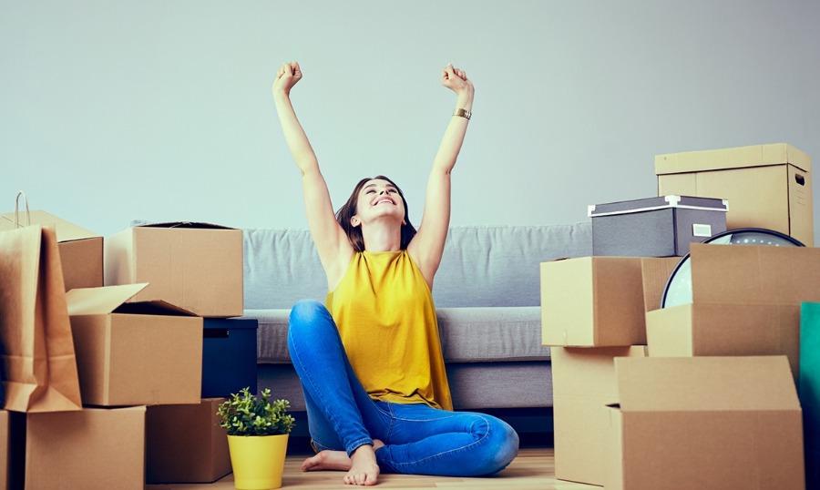 ao mudar de cidade é preciso avaliar vários fatores antes de decidir. Na imagem está uma mulher em frente ao sofá, vestida de amarelo e cheia de caixas de mudança ao redor.