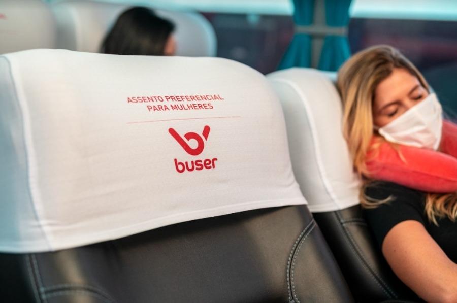 na foto, uma mulher dorme em assento preferencial feminino enquanto outra está sentada na poltrona de trás