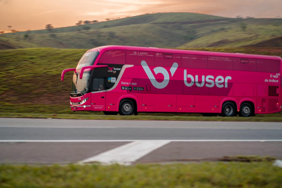 ônibus novo e seguro da Buser percorrendo estrada rodeado de montanhas e belas paisagens que demonstra que a Buser é confiável