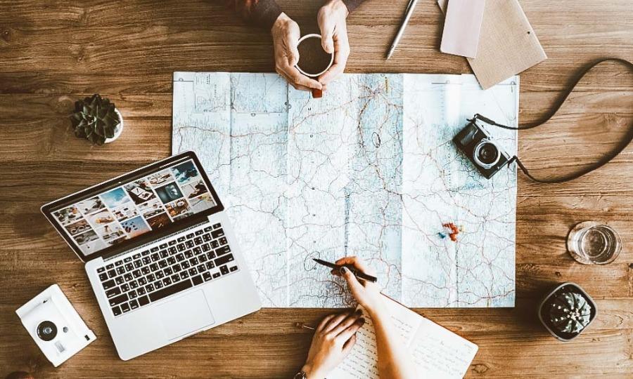duas pessoas com notebook e mapa segurando caneta e fazendo o planejamento de viagem
