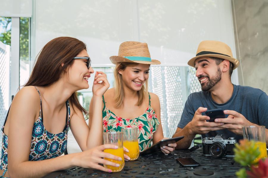 viajantes de chapéus tomando sucos com equipamento eletrônicos planejando a próxima viagem