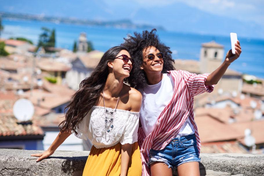 Na imagem estão duas mulheres viajantes lado a lado ilustrando como encontrar companhia para viajar