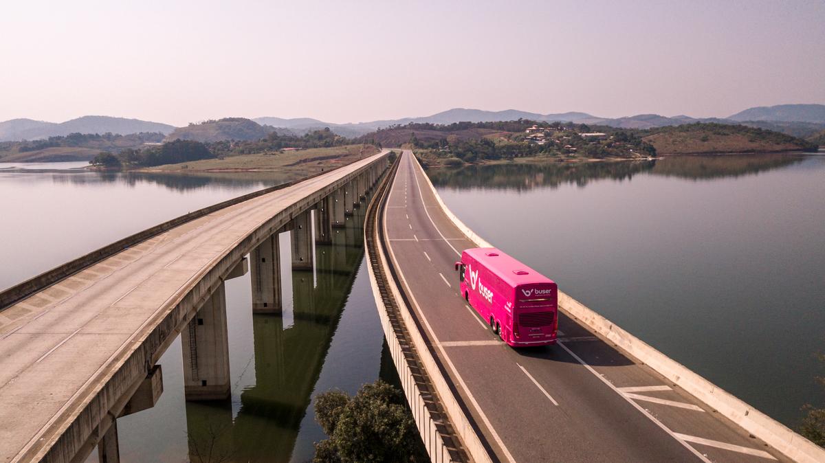 ônibus da BUser rosa por cima de um viaduto de uma represa em viagem que mostra que viajar de Buser é confiável