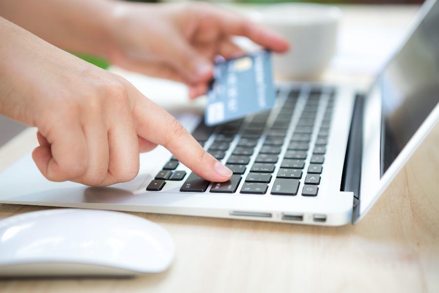 saiba como fazer pagamentos online com segurança para viajar. Na foto as mãos de uma mulher seguram um cartão de crédito e digita no teclado de um notebook